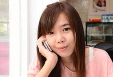 Teléfono sonriente y de discurso de la muchacha feliz Imagen de archivo libre de regalías