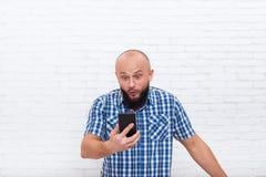 Teléfono sorprendido confundido barbudo casual de Smart de la célula de tenencia del hombre de negocios Fotos de archivo libres de regalías