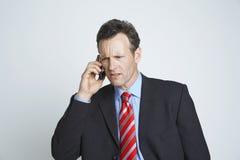 Teléfono tensado de Communicating On Cell del hombre de negocios fotos de archivo libres de regalías