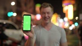 Teléfono turístico feliz joven de la demostración del hombre contra la vista de las calles en Chinatown en la noche metrajes