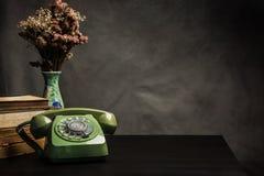 Teléfono viejo en la tabla, aún vida del vintage Foto de archivo libre de regalías