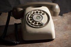 Teléfono viejo en una tabla, teléfono viejo del vintage con el disco rotatorio en fondo de madera del grunge de la tabla Imagen de archivo