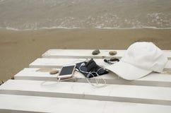 Teléfono y accesorios en la playa Fotografía de archivo