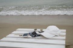 Teléfono y accesorios en la playa Imagen de archivo