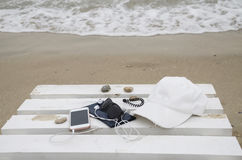 Teléfono y accesorios en la playa Fotos de archivo libres de regalías