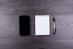 Teléfono y cuaderno Fotografía de archivo libre de regalías