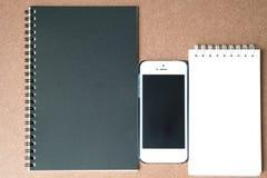 Teléfono y cuadernos en el fondo marrón Fotos de archivo