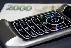 Teléfono y dinero. Fotografía de archivo