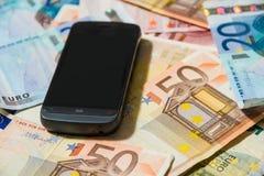 Teléfono y dinero Fotos de archivo libres de regalías
