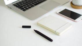 Teléfono y libreta del ordenador en la tabla blanca del fondo Imagenes de archivo