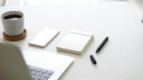 Teléfono y libreta del ordenador en la tabla blanca del fondo Imagen de archivo