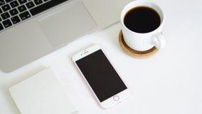 Teléfono y libreta del ordenador en la tabla blanca del fondo Foto de archivo libre de regalías
