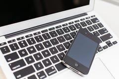 Teléfono y ordenador portátil elegantes Fotografía de archivo libre de regalías