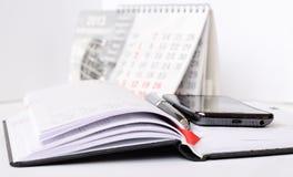 Teléfono y pluma en un cuaderno Fotos de archivo