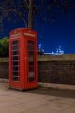 Teléfono y puente rojos en la noche, Londres, Inglaterra de la torre Foto de archivo