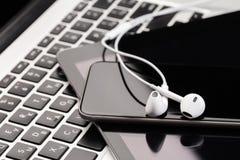 Teléfono y tableta con los auriculares blancos en el teclado del ordenador portátil foto de archivo