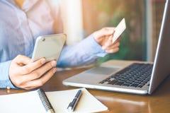 Teléfonos celulares del uso del control de la mano de la mujer de negocios y tarjetas de crédito al mA Fotografía de archivo libre de regalías