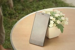 Teléfonos móviles con las flores en la tabla Imagenes de archivo