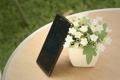 Teléfonos móviles con las flores en la tabla Fotos de archivo