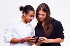 Teléfonos móviles de los asimientos de las mujeres Foto de archivo