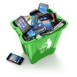 Teléfonos móviles en bote de basura en el fondo blanco Utiliza Fotografía de archivo libre de regalías