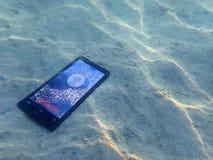 Teléfonos móviles en la arena debajo de la agua de mar Imágenes de archivo libres de regalías