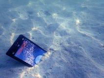 Teléfonos móviles en la arena debajo de la agua de mar Imagen de archivo