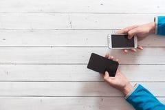 Teléfonos móviles en manos Foto de archivo