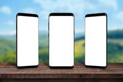 Teléfonos móviles múltiples en el escritorio de madera para el producto, presentación del app Imagen de archivo