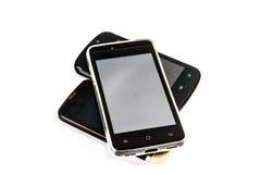 Teléfonos móviles usados en el fondo blanco foto de archivo libre de regalías