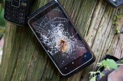 Teléfonos móviles viejos quebrados clavados al árbol imagen de archivo