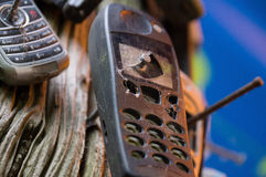 Teléfonos móviles viejos quebrados clavados al árbol foto de archivo