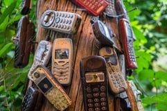 Teléfonos móviles viejos quebrados clavados al árbol imagenes de archivo