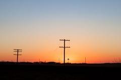 Telégrafo postes silueteados en salida del sol de oro imagen de archivo