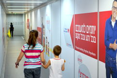 Tel Aviv Airport Jet Bridge. Two kids aged 12 and 6 boarding the airplane with Hebrew advertisements in the background at Tel Aviv Airport  (TLV or Ben Gurion Royalty Free Stock Photography