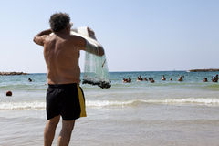 Pêcheur tirant le filet sur la plage de Tel Aviv Photo libre de droits