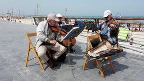 Tel Aviv, Israël - 2019-04-27 - musiciens pluss âgé de ficelle à la plage avec le bruit 3 - regardant vers la plage banque de vidéos