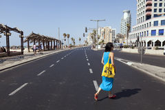 Summer at the Beach in Tel-Aviv. Tel-Aviv, Israel - August 18th, 2012: An adult Caucasian woman in her early 30's crossing the street that stretches along the Royalty Free Stock Photos
