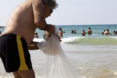 Fisherman Pulling Net on Tel-Aviv Beach Royalty Free Stock Photos