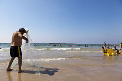 Fisherman Pulling Net on Tel-Aviv Beach Stock Images
