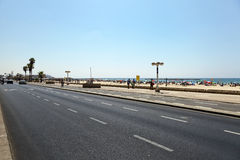 Summer at the Beach in Tel-Aviv. Tel-Aviv, Israel - August 18th, 2012: A view of the Tel-Aviv beach and boardwalk full with on vacation, from the other side of Royalty Free Stock Images