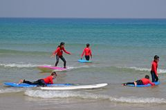 Tel-Aviv, Israel - 04/05/2017: Children catch a wave. Children`s school of surfing on Mediterranean Sea. Tel-Aviv, Israel - 04/05/2017: Children catch a wave Royalty Free Stock Image