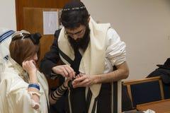 TEL AVIV, ISRAEL - 19 DE ENERO DE 2018: Un hombre ortodoxo, mantón de rezo que llevaba, puso un Tefillin judío en el brazo del ho Imagenes de archivo