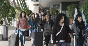 Tel Aviv, Israel - January 2018. People arrivign at the airport terminal. Tel Aviv, Israel - January 2018. Passengers walking into the airport terminal stock video