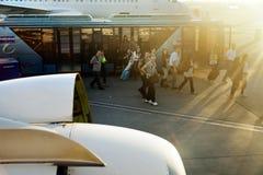 Passagiere weg vom Bus und auf ein Flugzeug Stockfotografie