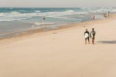 Tel Aviv Israel - November 3, 2018: Två unga surfare med surfingbrädor går den sandiga stranden av medelhavet royaltyfri foto