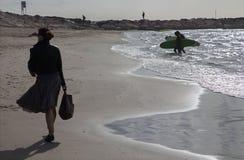 Tel Aviv - a silhueta da mulher e de surfistas andados na praia Imagens de Stock