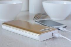 Tel?fono celular de los gastos bancarios del poder en la tabla de cocina imágenes de archivo libres de regalías