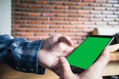 Tel?fono elegante de la pantalla del verde de la maqueta de la tenencia de la mano fotografía de archivo libre de regalías