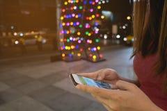 Tel?fono m?vil del uso de la mujer, noche en la ciudad fotos de archivo libres de regalías